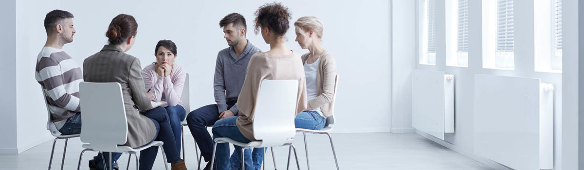People sitting in a circle with psychologist in group therapy