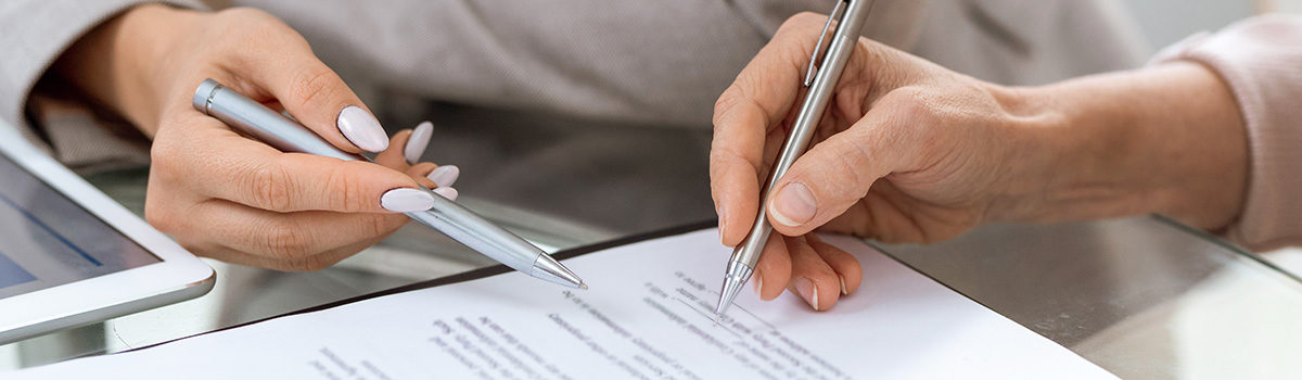 Human hands with pens over financial document in moment of putting signature after discussing its points