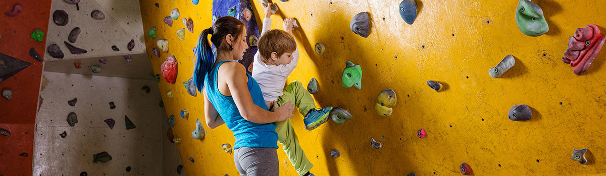 young-female-bouldering-instructor-helping-boy-PDAJKE8